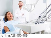 Купить «Young female is sitting satisfied after treatment in dental office», фото № 28450489, снято 10 июля 2017 г. (c) Яков Филимонов / Фотобанк Лори