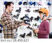 Купить «Seller assisting boy in choosing roller-skates», фото № 28450621, снято 21 декабря 2016 г. (c) Яков Филимонов / Фотобанк Лори