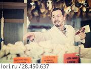 Купить «Seller offering displayed sorts of meat», фото № 28450637, снято 2 января 2017 г. (c) Яков Филимонов / Фотобанк Лори