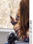 "Купить «Девушка со смартфоном у окна в вагоне электропоезда ""Ласточка"" на МЦК», фото № 28451489, снято 30 марта 2018 г. (c) Алёшина Оксана / Фотобанк Лори"