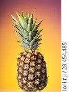 Купить «Large ripe pineapple with rind and stem on bright background», фото № 28454485, снято 22 декабря 2017 г. (c) Сергей Молодиков / Фотобанк Лори