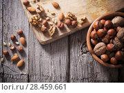 Купить «Mixed nuts on old wooden background», фото № 28459661, снято 21 ноября 2016 г. (c) Майя Крученкова / Фотобанк Лори