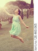 Купить «young brunette female in dress jumping at the park», фото № 28460065, снято 18 апреля 2017 г. (c) Яков Филимонов / Фотобанк Лори