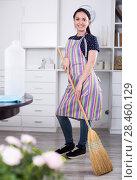 Купить «Cheerful girl sweeping floor», фото № 28460129, снято 9 апреля 2017 г. (c) Яков Филимонов / Фотобанк Лори