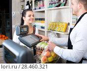 Купить «Man seller helping customer to weigh purchases», фото № 28460321, снято 23 ноября 2016 г. (c) Яков Филимонов / Фотобанк Лори