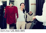 Купить «Smiling couple purchasing dress and blouse», фото № 28460485, снято 24 октября 2016 г. (c) Яков Филимонов / Фотобанк Лори