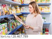 Купить «Adult positive woman buyer with cake layers of grocery food store», фото № 28467789, снято 11 апреля 2018 г. (c) Яков Филимонов / Фотобанк Лори