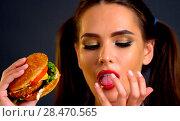 Купить «Woman eating hamburger. Girl wants to eat fast food.», фото № 28470565, снято 30 мая 2020 г. (c) Gennadiy Poznyakov / Фотобанк Лори