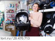 Купить «woman shows infant's car cradle», фото № 28470713, снято 19 декабря 2017 г. (c) Яков Филимонов / Фотобанк Лори