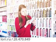 Купить «Female customer is choosing hair dye in the hair care shop», фото № 28470849, снято 22 марта 2018 г. (c) Яков Филимонов / Фотобанк Лори
