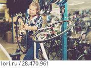 Купить «Female worker is replacing wheel of bicycle», фото № 28470961, снято 13 сентября 2017 г. (c) Яков Филимонов / Фотобанк Лори
