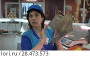Купить «Продавщица показывает покупателю вяленую соленую камбалу на рыбном рынке», видеоролик № 28473573, снято 21 мая 2018 г. (c) А. А. Пирагис / Фотобанк Лори