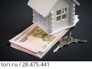 A bundle of Russian rubles, the keys to a future home and a mock-up of house on a black background. Стоковое фото, фотограф Олег Белов / Фотобанк Лори