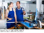 Купить «Workman 20-30 years old is explaining work on circular saw to yo», фото № 28475957, снято 19 июля 2017 г. (c) Яков Филимонов / Фотобанк Лори