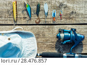 Купить «objects for fishing on a wooden pier close-up - hooks, baits, coil and hat», фото № 28476857, снято 16 июня 2016 г. (c) Константин Лабунский / Фотобанк Лори