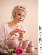Young beautiful blond woman eating macaroon while having tea-party. She is very satisfacted. Short hair and pink colors - modern style. Стоковое фото, фотограф Kirill Kedrinskiy / Ingram Publishing / Фотобанк Лори