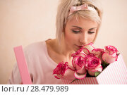 Young beautiful woman holding bow with bouquet of pink roses inside. She is very satisfacted. Valentine's day or international women's day celebration. Стоковое фото, фотограф Kirill Kedrinskiy / Ingram Publishing / Фотобанк Лори