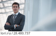 Portrait of handsome confident young businessman standing arms crossed, looking at camera. Стоковое фото, фотограф Kirill Kedrinskiy / Ingram Publishing / Фотобанк Лори