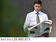 Handsome businessman or manager, in front of modern office architecture, reading newspaper. Стоковое фото, фотограф Kirill Kedrinskiy / Ingram Publishing / Фотобанк Лори