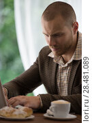 Купить «Young businessman working at cafe using laptop», фото № 28481089, снято 20 июля 2014 г. (c) Ingram Publishing / Фотобанк Лори