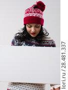 Купить «Young smiling winter woman wearing beanie knitted hat and dress holding blank copyspace», фото № 28481337, снято 15 октября 2014 г. (c) Ingram Publishing / Фотобанк Лори