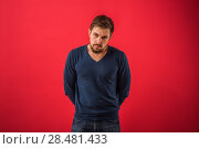 Serious man looking at camera standing against red background. Стоковое фото, агентство Ingram Publishing / Фотобанк Лори