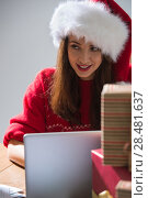 Купить «Young pretty woman wearing Santa Claus hat wrapping Christmas gift at her desk and responding to children messages and wishes by email», фото № 28481637, снято 12 ноября 2014 г. (c) Ingram Publishing / Фотобанк Лори