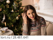 Купить «Beautiful woman wearing winter outfit sitting on couch at home near Christmas tree», фото № 28481641, снято 12 ноября 2014 г. (c) Ingram Publishing / Фотобанк Лори