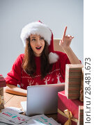Купить «Young pretty woman wearing Santa Claus hat wrapping Christmas gift at her desk and responding to children messages and wishes by email», фото № 28481673, снято 12 ноября 2014 г. (c) Ingram Publishing / Фотобанк Лори