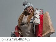 Купить «Shopping, sale, gifts, christmas, xmas concept - smiling woman in knitted dress with shopping bags», фото № 28482405, снято 20 ноября 2014 г. (c) Ingram Publishing / Фотобанк Лори