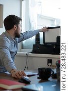 Купить «Handsome businessman scanning and printing document in office», фото № 28483221, снято 29 января 2015 г. (c) Ingram Publishing / Фотобанк Лори