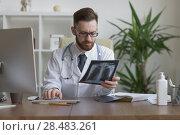 Купить «Thoughtful doctor holding chest and lungs xray in medical office», фото № 28483261, снято 5 июня 2015 г. (c) Ingram Publishing / Фотобанк Лори