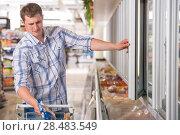 Купить «Man in a supermarket standing in front of the freezer looking for his favorite frozen food», фото № 28483549, снято 17 июля 2013 г. (c) Ingram Publishing / Фотобанк Лори