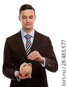 Купить «Young happy business man putting money in the piggybank over white background», фото № 28483577, снято 2 февраля 2013 г. (c) Ingram Publishing / Фотобанк Лори