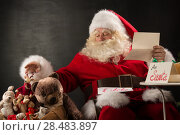 Купить «Santa Claus sitting at home at comfortable armchair holding envelope and reading children's letters and wishes and choosing toys from big sack near him», фото № 28483897, снято 12 января 2013 г. (c) Ingram Publishing / Фотобанк Лори