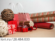 Купить «Christmas background with red and natural decorations, gift boxes, little bags with presents», фото № 28484033, снято 3 ноября 2012 г. (c) Ingram Publishing / Фотобанк Лори