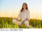 Купить «Yoga woman meditating on green grass against the sun», фото № 28484153, снято 22 июня 2013 г. (c) Ingram Publishing / Фотобанк Лори