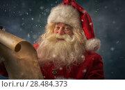 Купить «Portrait of happy Santa Claus reading Christmas letter outdoors at north pole under snowfall», фото № 28484373, снято 25 сентября 2013 г. (c) Ingram Publishing / Фотобанк Лори