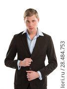 Купить «Portrait of a confident young male executive buttoning his cuff on white background», фото № 28484753, снято 23 февраля 2013 г. (c) Ingram Publishing / Фотобанк Лори