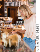 Купить «Positive young woman at the bakery store choosing what she wants to by and placing order to seller», фото № 28484921, снято 16 июля 2013 г. (c) Ingram Publishing / Фотобанк Лори
