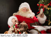 Купить «Santa Claus sitting at home at comfortable armchair holding envelope and reading children's letters and wishes and choosing toys from big sack near him», фото № 28485029, снято 12 января 2013 г. (c) Ingram Publishing / Фотобанк Лори