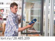Купить «Man in a supermarket standing in front of the freezer looking for his favorite frozen food», фото № 28485209, снято 17 июля 2013 г. (c) Ingram Publishing / Фотобанк Лори