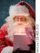 Купить «Portrait of happy Santa Claus opening gift box outdoors at North Pole. Magical light from box on his face», фото № 28485313, снято 25 сентября 2013 г. (c) Ingram Publishing / Фотобанк Лори