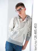 Купить «Portrait of young fashionable man leaning on white wall and wearing glasses. He is trendy fashionable or maybe gay», фото № 28485453, снято 13 апреля 2013 г. (c) Ingram Publishing / Фотобанк Лори