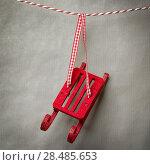 Купить «Santa's fairy Christmas decorative sleigh hanging on a ribbon. Old grunge gray paper background», фото № 28485653, снято 3 ноября 2012 г. (c) Ingram Publishing / Фотобанк Лори