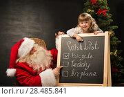 Купить «Santa Claus with child sitting near chalkboard with wish list and checking it», фото № 28485841, снято 25 мая 2013 г. (c) Ingram Publishing / Фотобанк Лори