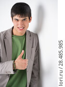 Купить «Happy smiling young man leaning against white wall and showing thumbs up», фото № 28485985, снято 13 апреля 2013 г. (c) Ingram Publishing / Фотобанк Лори