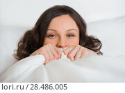 Купить «Beautiful young girl hides her face in bed and flirting», фото № 28486005, снято 18 декабря 2012 г. (c) Ingram Publishing / Фотобанк Лори