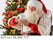 Santa Claus sitting in rocking chair near Christmas Tree at home and drinking hot tea or coffee. Стоковое фото, фотограф Kirill Kedrinskiy / Ingram Publishing / Фотобанк Лори