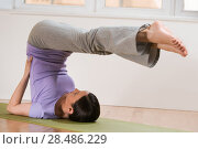 Купить «Woman in a traditional stretching yoga pose at home or gym», фото № 28486229, снято 27 ноября 2012 г. (c) Ingram Publishing / Фотобанк Лори